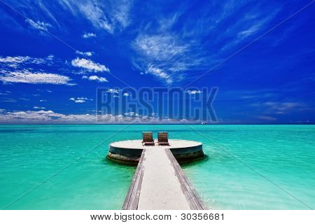 Two deck chairs on stunning empty tropical beach