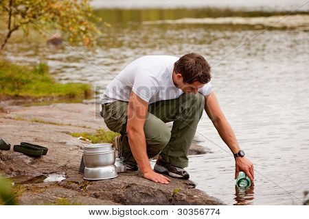 A young male adult fetching fresh water from a forest lake