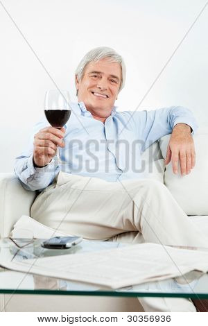 Happy senior man toasting with glass of red wine