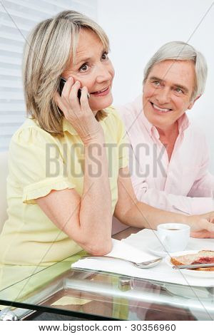 Senior woman talking to cell phone at breakfast table