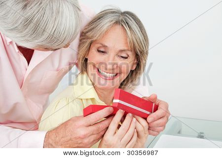 Happy smiling senior woman receiving gift from her husband