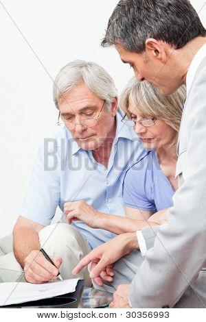 Senior man ondertekening contract met financiële adviseur thuis