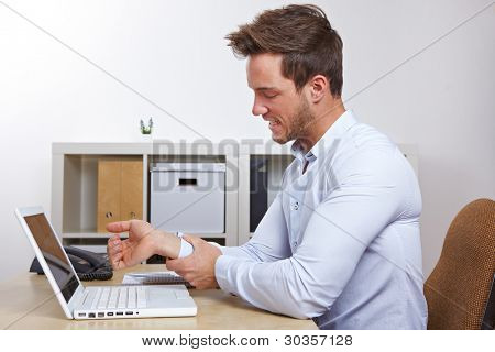 Hombre de negocios en la oficina con síndrome RSI mano su dolor