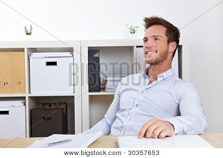 Happy business man relaxing in office at desk leaning back