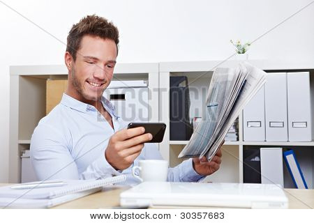 Young business man in office looking for job with smartphone and newspaper