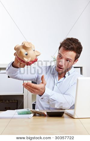 Shocked university student shaking empty piggy bank at desk
