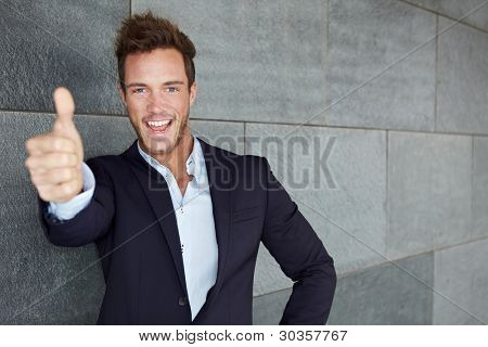 Happy business man in urban city holding thumbs up