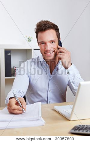 Happy business man in office making cell phone call and taking notes