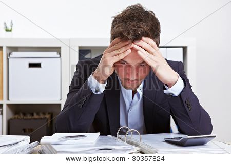 Business man in office with burnout syndrome at desk
