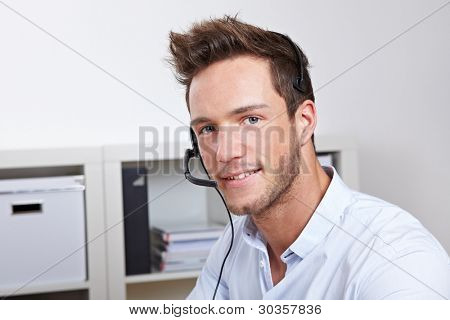 Helpful phone support agent with headset in callcenter office