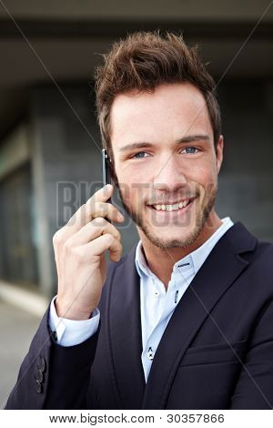 Smiling business man using cell phone in urban city