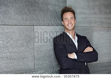 Content business man leaning on wall with his arms crossed