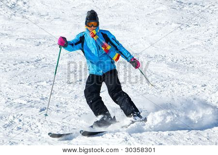 Young male skier turning in powder snow; blue jacket; black pant; horizontal orientation