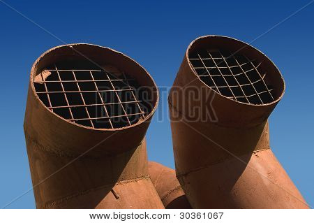 Two Ventilation Pipes Against Blue Sky