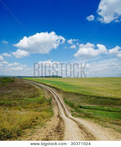 winding rural road under deep blue cloudy sky
