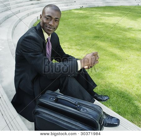 Businessman with briefcase sitting outdoors