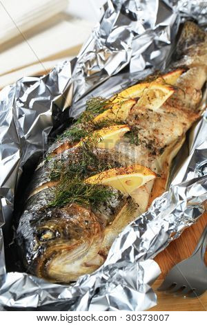 Grilled fresh trout with herbs and lemon on aluminium foil