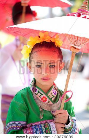 CHIANG MAI, THAILAND - FEBRUARY 4: Traditionally dressed girl in procession on Chiang Mai 36th Flower Festival on February 4, 2012 in Chiang Mai, Thailand