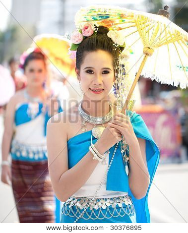 CHIANG MAI, THAILAND - FEBRUARY 4: Traditionally dressed woman in procession on Chiang Mai 36th Flower Festival on February 4, 2012 in Chiang Mai, Thailand