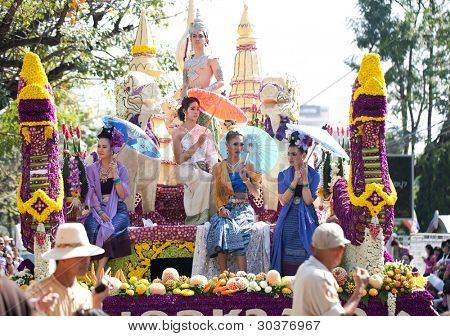CHIANG MAI, THAILAND - FEBRUARY 4: Womans on flower decorated cart on Chiang Mai 36th Flower Festival on February 4, 2012 in Chiang Mai, Thailand