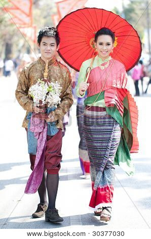 CHIANG MAI, THAILAND - FEBRUARY 4: Traditionally dressed Thai couple in procession on Chiang Mai 36th Flower Festival on February 4, 2012 in Chiang Mai, Thailand