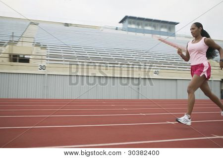 Female athlete running on track