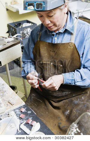 Female welder using pliers