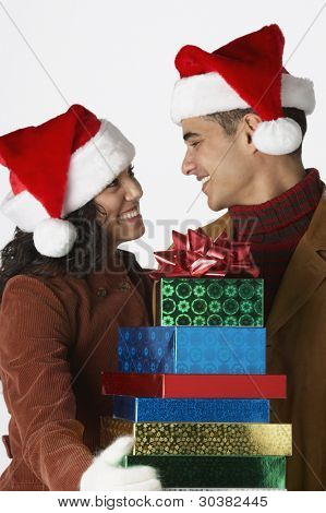 Young couple wearing Santa hats with gifts