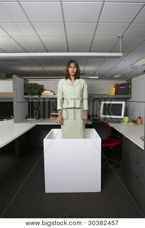 Businesswoman standing in office cubicle