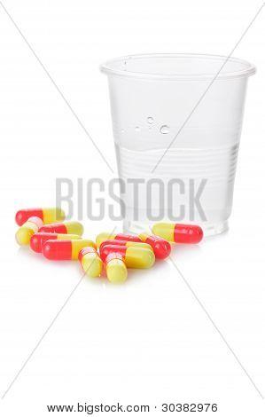 Farmacia. Pastillas antibióticas y vaso plástico de agua