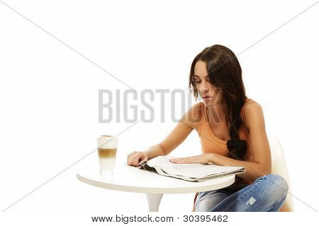 young woman reading newspaper at a table with latte macchiato coffee