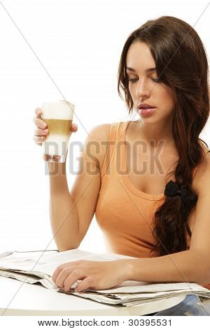 young woman sitting at a table reading newspaper holding latte macchiato coffee
