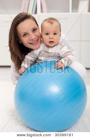 Young woman and baby playing with large ball