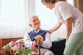Senior Man With A Walking Stick Being Comforted By Nurse In The Hospice poster
