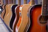 Row Of Acoustic Guitars In A Music Instruments Shop. Guitar Part, Wooden Guitar Body poster