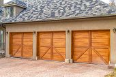 Luxurious Exterior Of A House With Stylish Brown Wooden Garage Doors poster