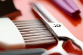 Metal Scissors And Brush Close-up Photography. Professional Hairdresser Tool On Red Background. Stee poster