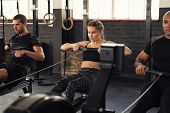 Young man and beautiful woman working out with rowing machine at crossfit gym. Athletic class doing  poster