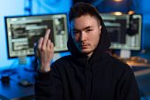 cybercrime, hacking and technology concept - young asian hacker wearing hoodie showing middle finger poster