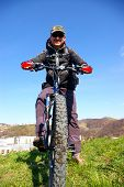 image of sakhalin  - Man on bicycle with rucksack on background blue sky and peak of mountain - JPG