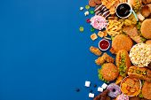 Fast Food Dish On Blue Background. Take Away Unhealthy Set Including Burgers, Sauces, French Fries,  poster
