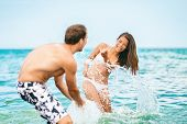 Beach fun couple playing in ocean water swimming splashing water at each other in swimsuits. Summer  poster