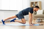 sport, fitness and healthy lifestyle concept - man with tablet computer doing running plank exercise poster