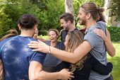 Group Of Happy People Embracing Each Other After Workout. Men And Women In Fitness Apparels Forming  poster