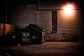 stock photo of dumpster  - A dirty dark shadowy and dangerous looking urban back-alley at night time with garbage dumpster.