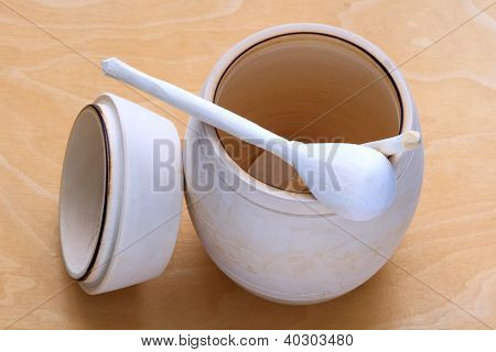 a barrel of honey with spoon