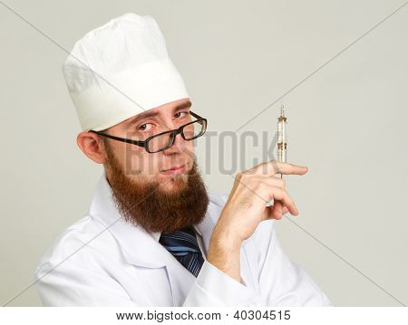 Portrait Of Young Happy Smiling Doctor With Syringe