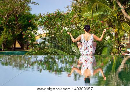 Young woman in lotus pose surrounded by tropical scenery