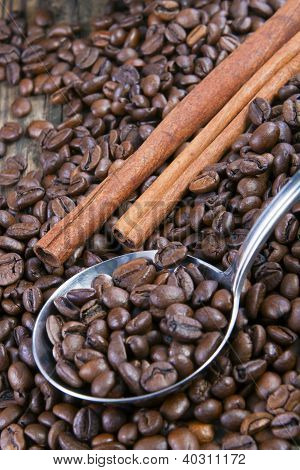 Coffee Beans And Cinnamon On Wooden Table With A Spoon.