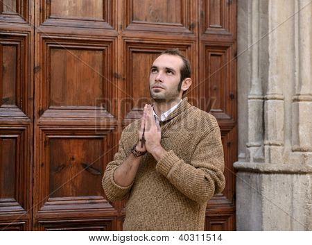 man monk praying to the front door of the church holding  rosary